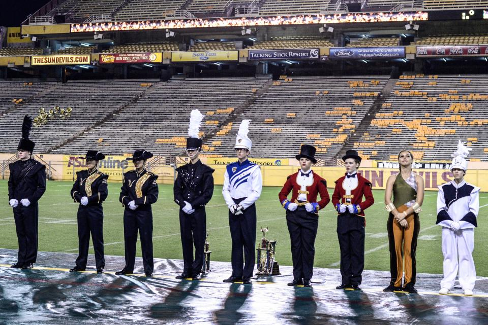 Members of high school marching bands line up at Sun Devil Stadium