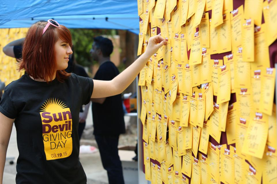 A student participates in Sun Devil Giving Day by pinning a note to a board.