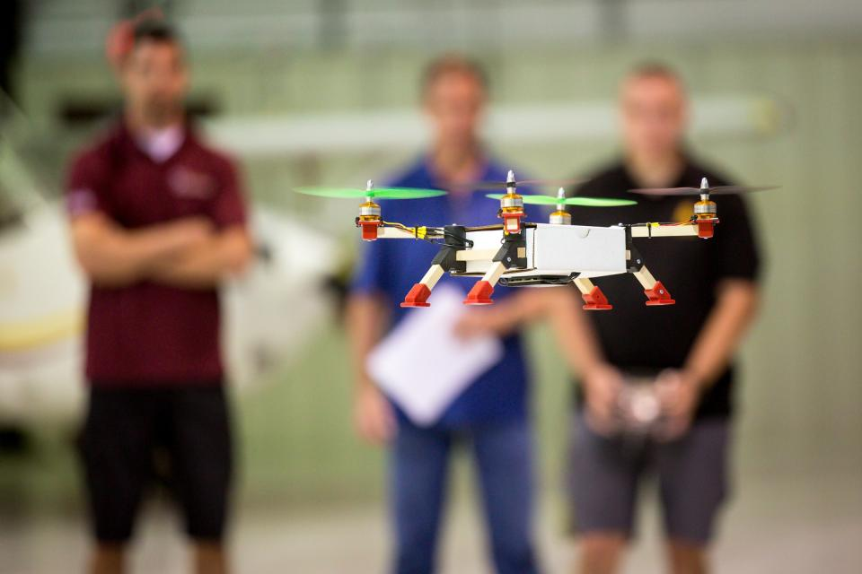 A student-made drone flies in an ASU hangar.