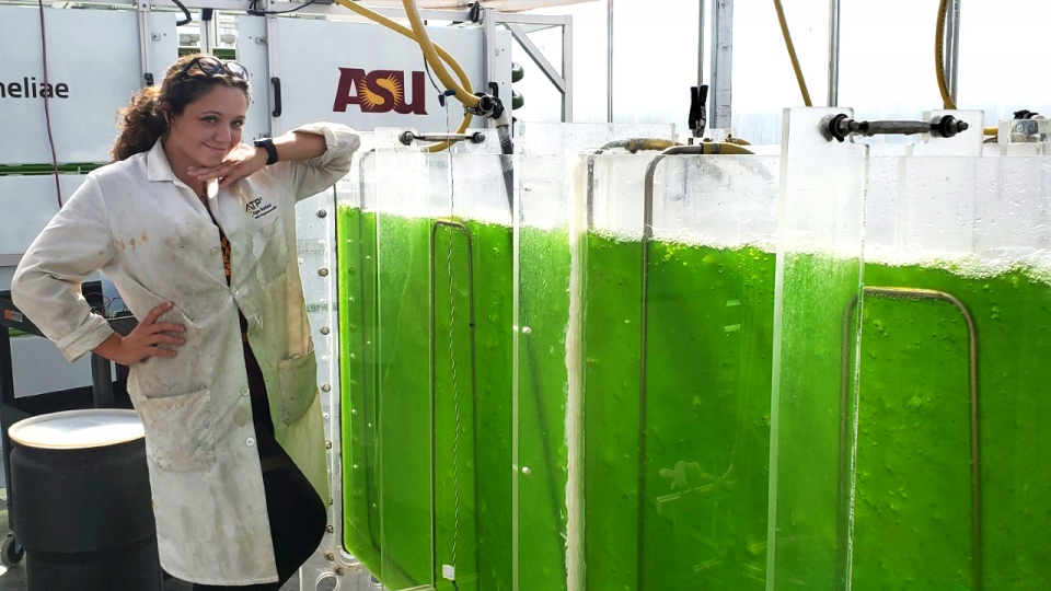 woman posing next to algae tanks