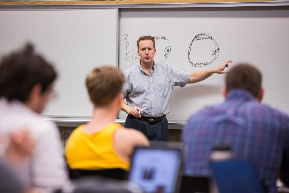 man at front of classroom pointing to whiteboard