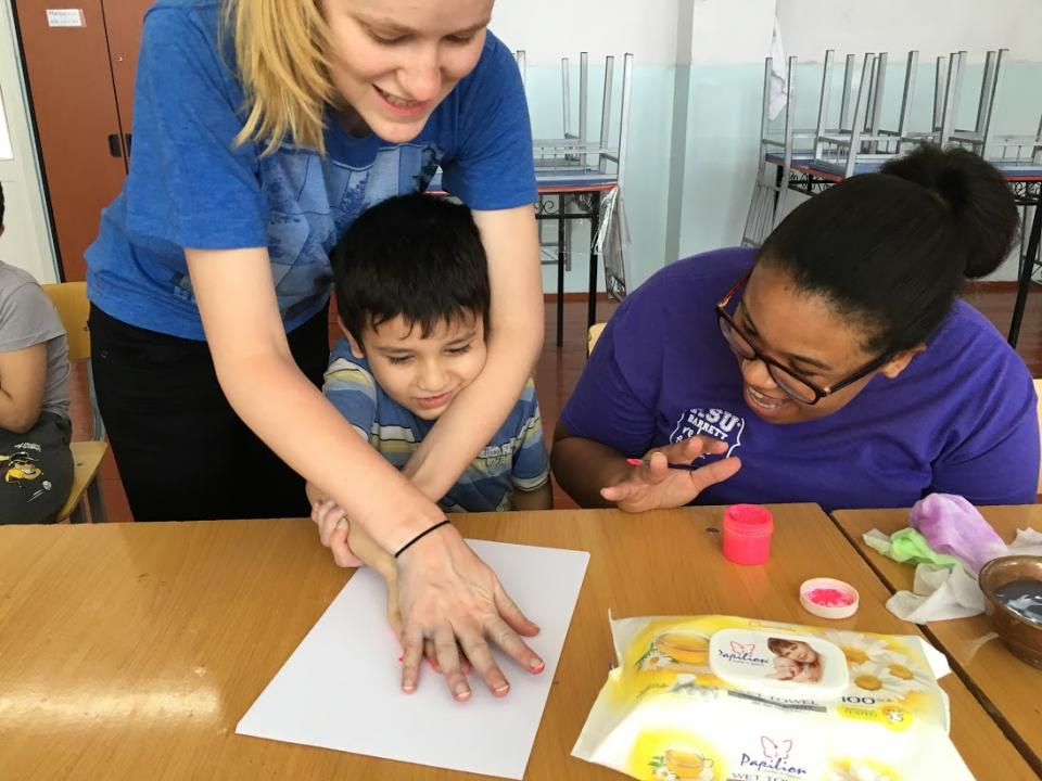 woman tracing hand prints with children