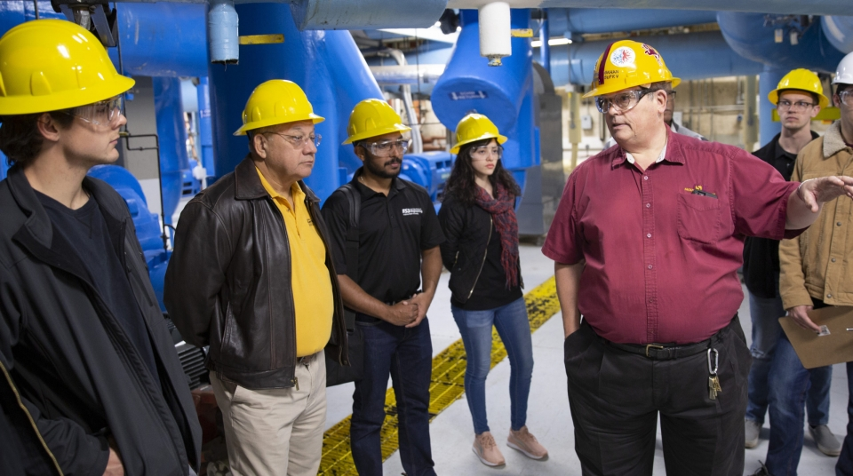 group of people talking in mechanical plant