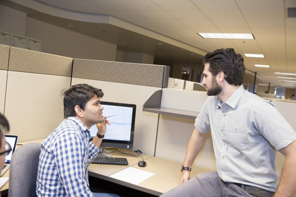 two men talking at a desk in front of a computer