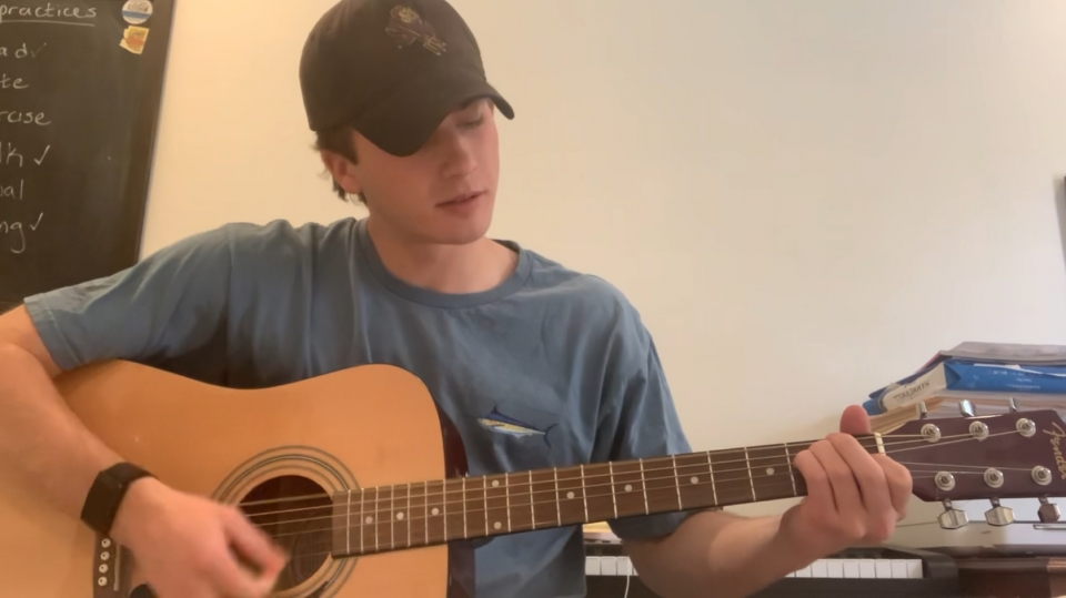 ASU student wearing hat with Sparky the Sun Devil on it while playing guitar