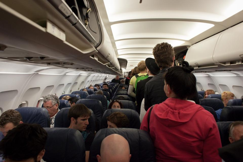 photo of passengers standing in plane aisle