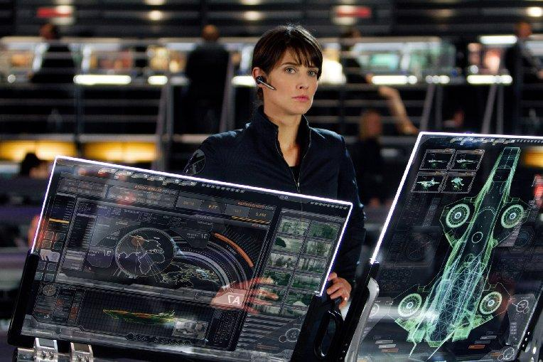 A woman stands at a military control panel.