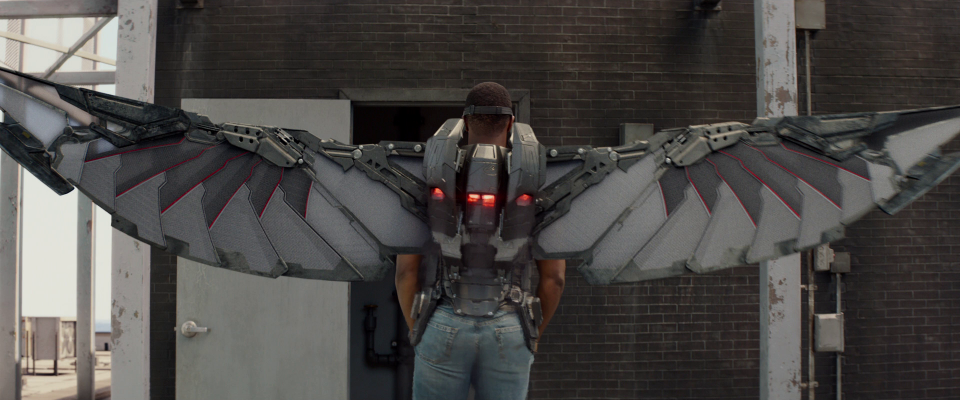 A man stands with a winged jetpack on.