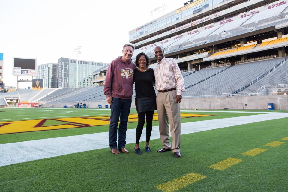 three people posing on stadium field