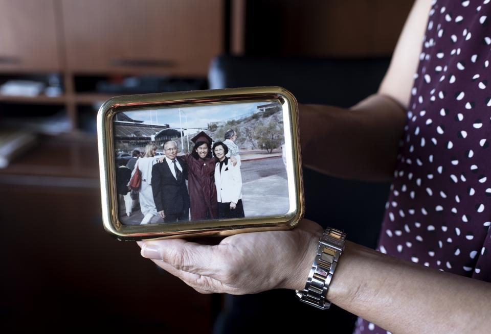 Arlene Chin shows a photo of herself and her parents, taken the day of her graduation from ASU.