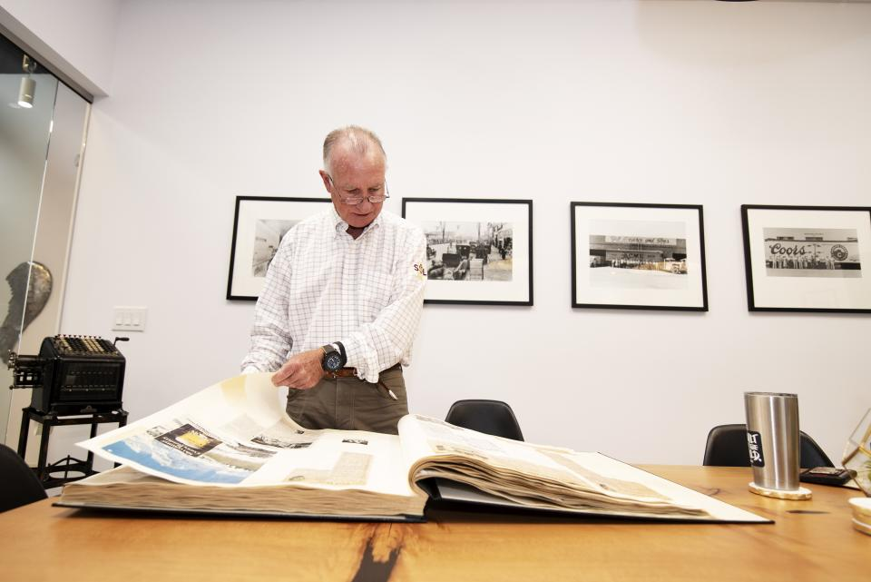 "Arthur ""Art"" Pearce looks through a scrapbook of a news clippings and other memorabilia documenting his grandfather Zebulon's legacy at ASU."