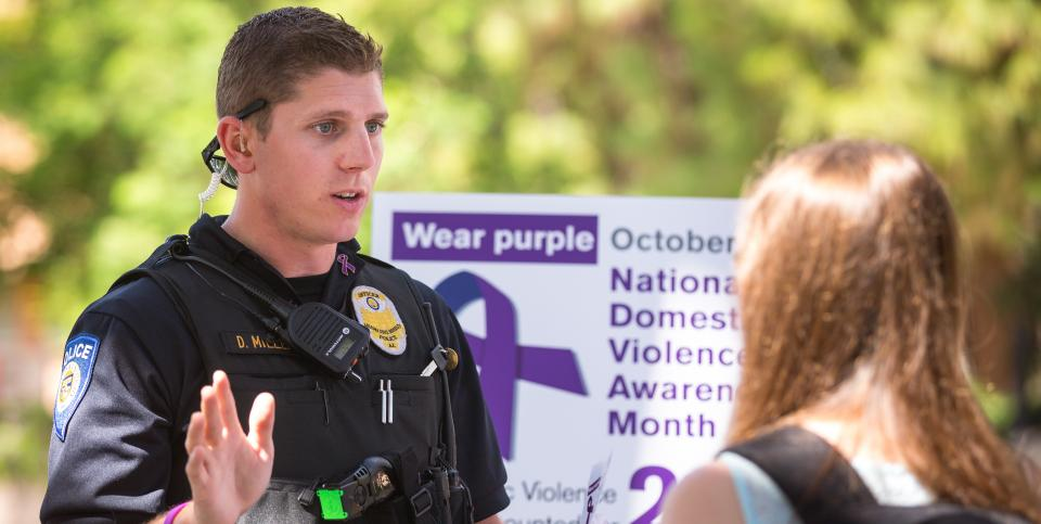 Photo of ASU Police Officer Daniel Miller and student during Domestic Violence Awareness Month