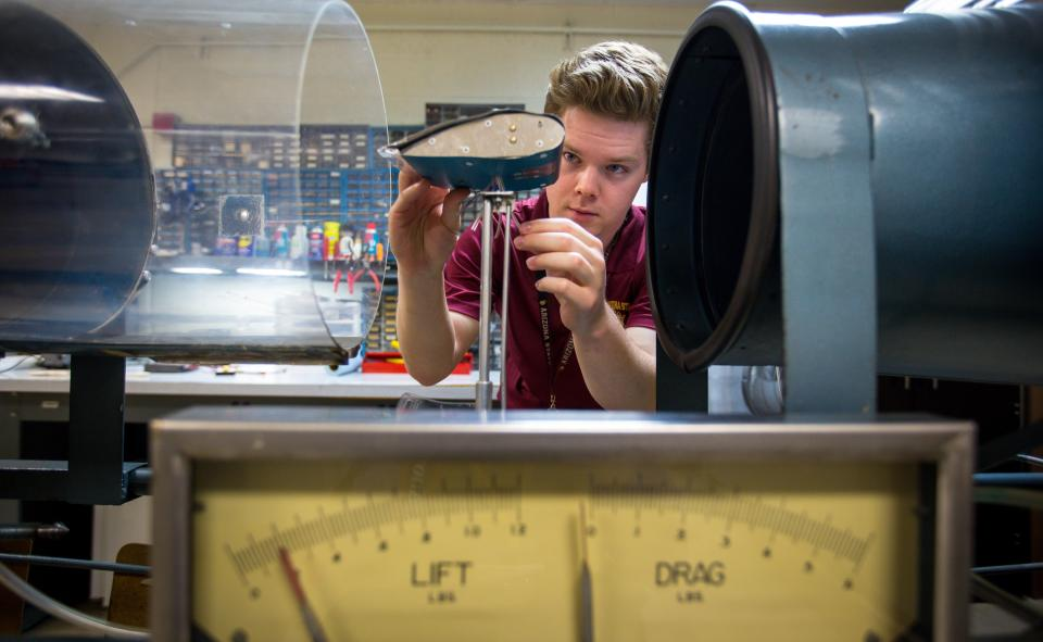 Aviation student Eamonn McIntyre adjusts a miniature wing in a wind tunnel.