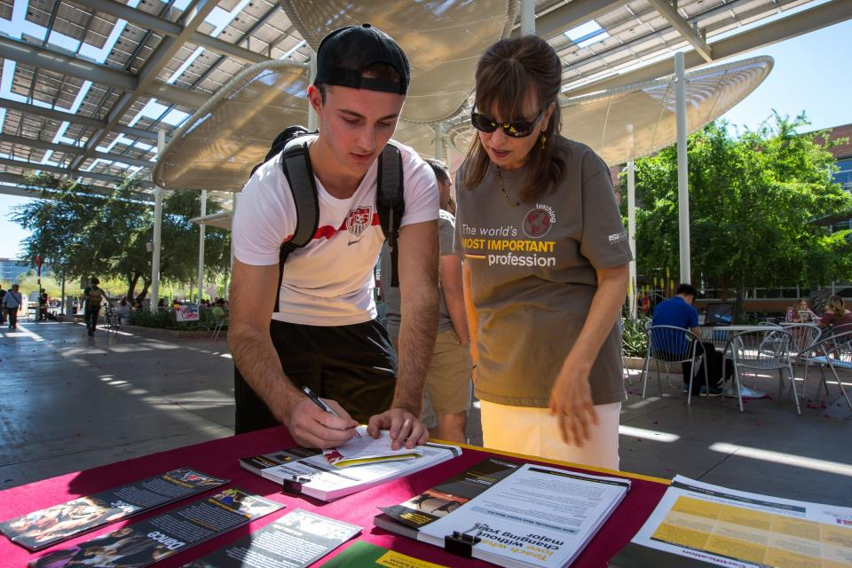 A student and an advisor talk at an education fair.