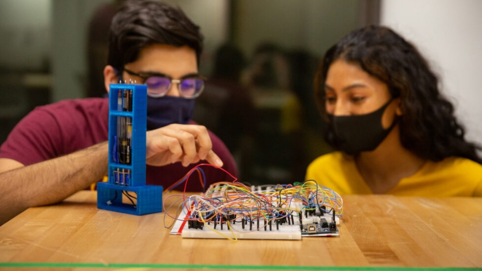 students working on electronic board