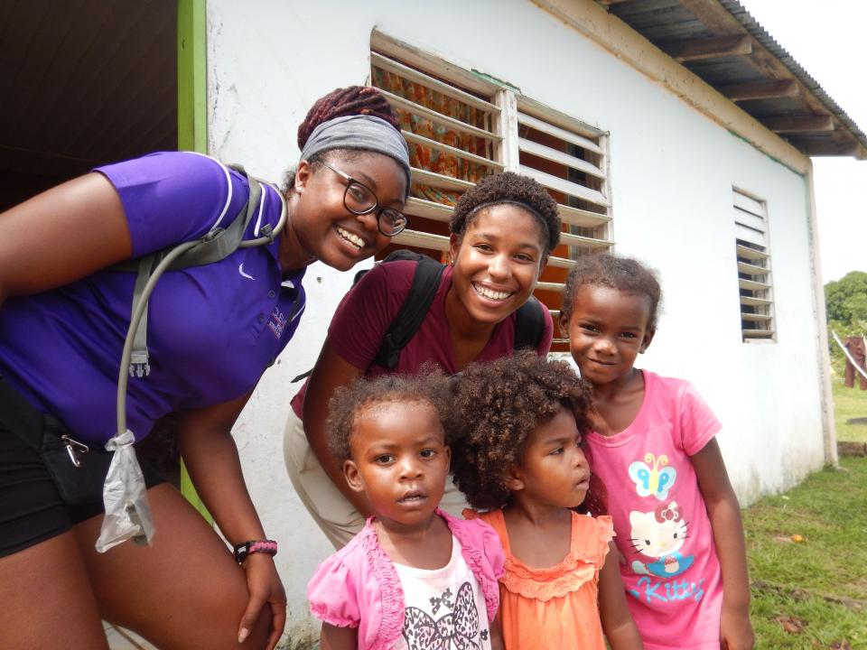 two women posing for a photo with children in Belize