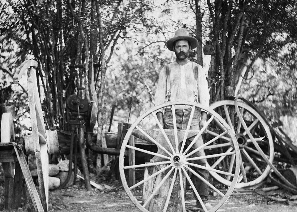 vintage photo of man behind wagon wheels