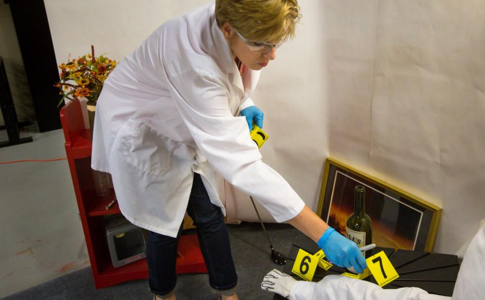 woman placing crime scene markers in lab simulation