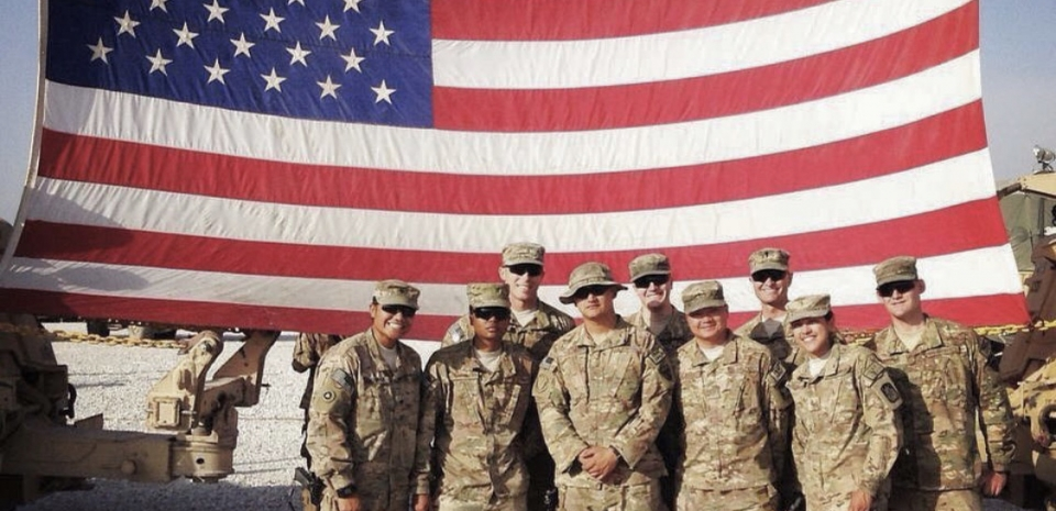 soldiers in front of an American flag