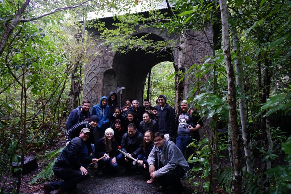 A group stands in front of a stone arch in a forest.