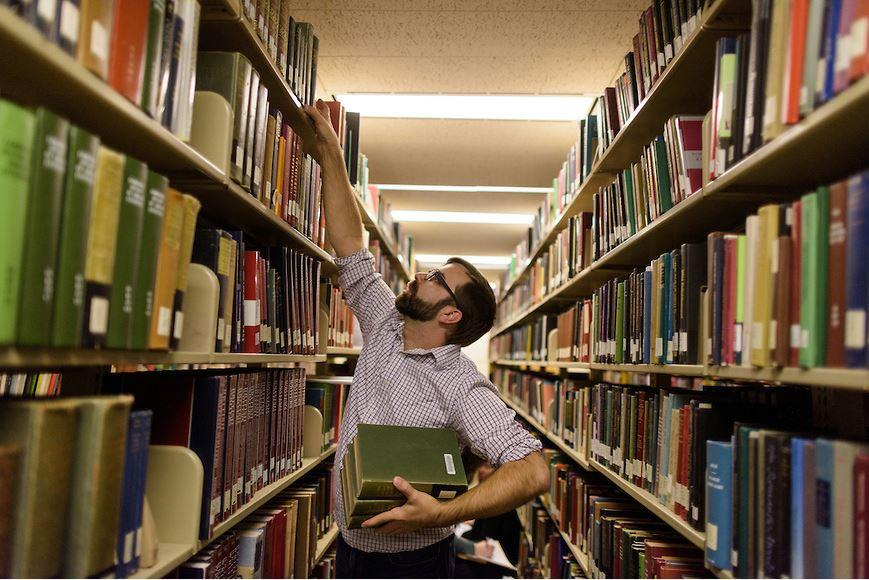student reaching for book on library shelf