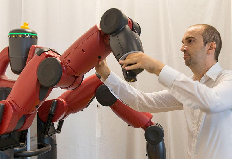 A man manually manipulated a robot's arm. The caption reads: Heni Ben Amor works with a Baxter robot in his lab. Photo by Jessica Hochreiter.