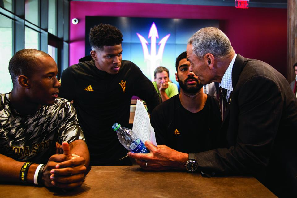 ASU Coach Herm Edwards talks with football players