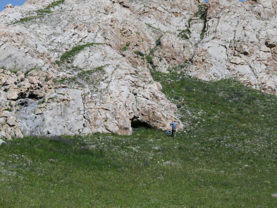 Photo of Dr. Perreault collecting data in front of a rock shelter in Mongolia