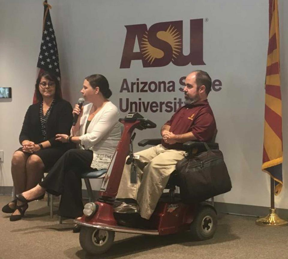 A man in an electric wheelchair sits by two women in front of an ASU logo