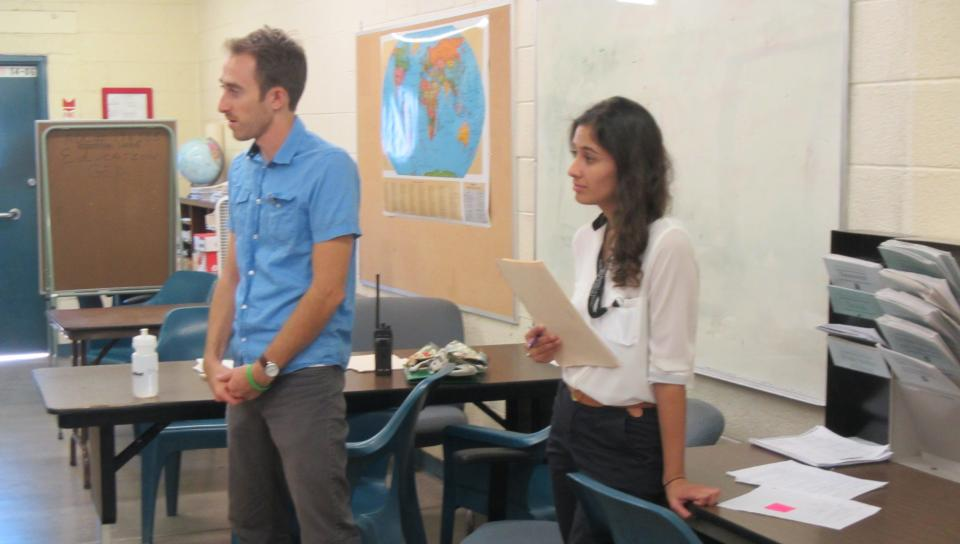 Two ASU students stand at the front of a classroom