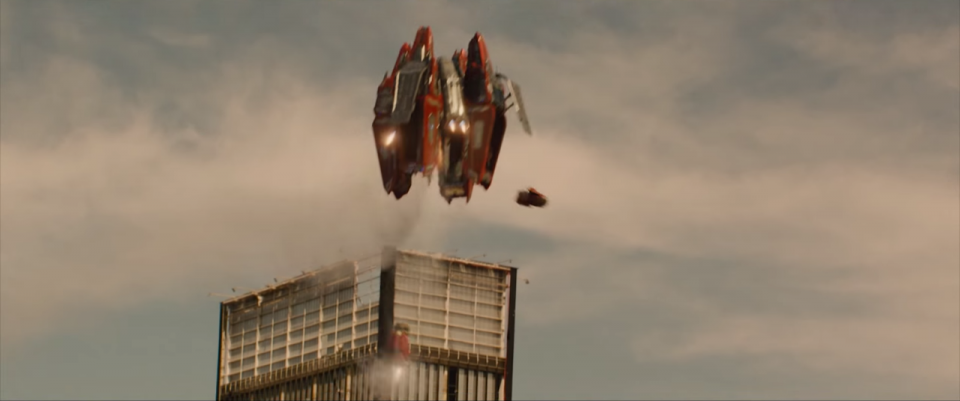 A flying machine bursts out of a building.