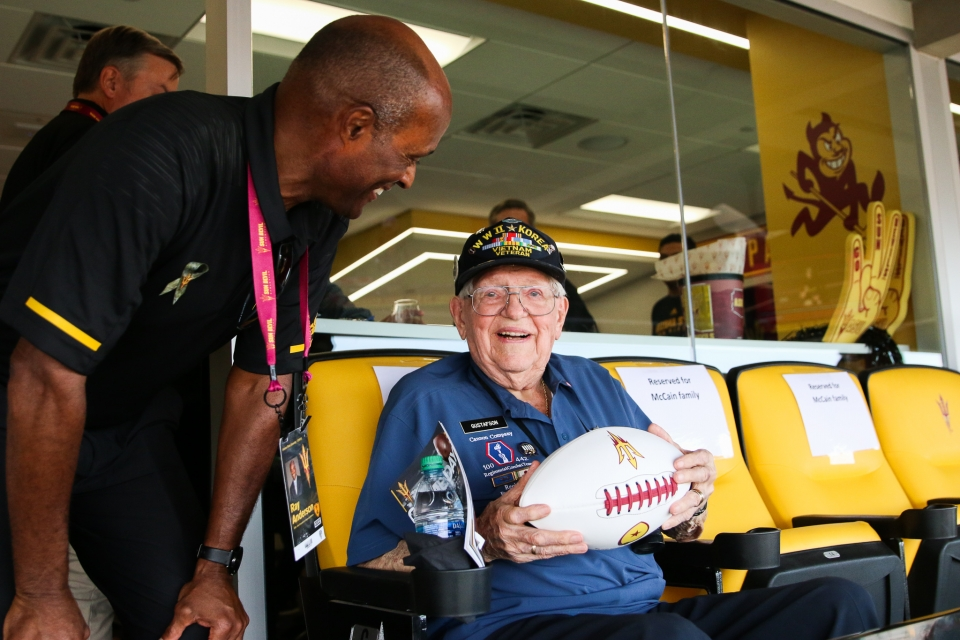 ASU alumnus and veteran Jerry Gustafson is presented with an autographed Herm Edwards football during Salute to Service