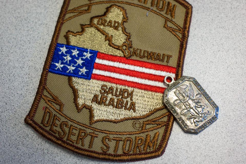 Dogtags are displayed next to a military patch.