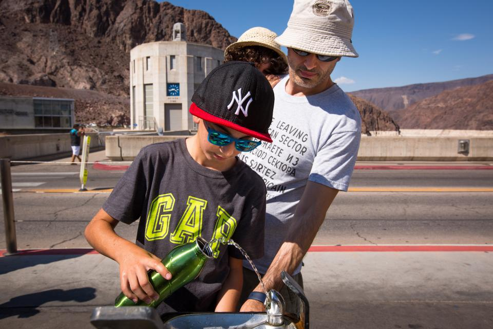 Tourists fill up a water bottle at Hoover Dam.