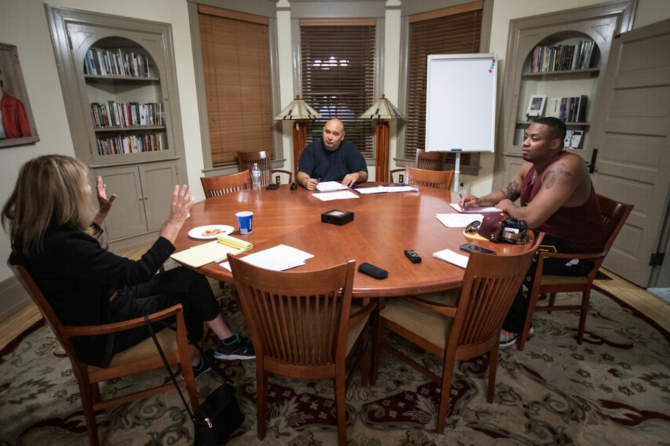 Three people talking at a round table