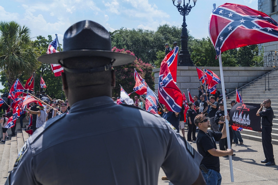 People carrying confederate flags and KKK banners protest at a government building as a Black guard looks on