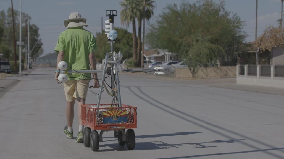 A man wearing a sun hat pulls a cart with a bunch of temperature sensors down a neighborhood street