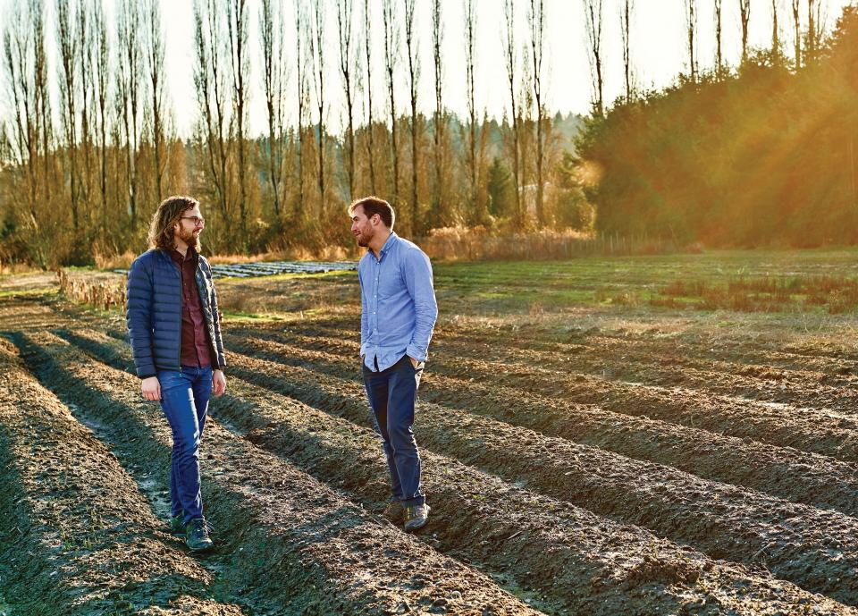 Two men stand in a farm field