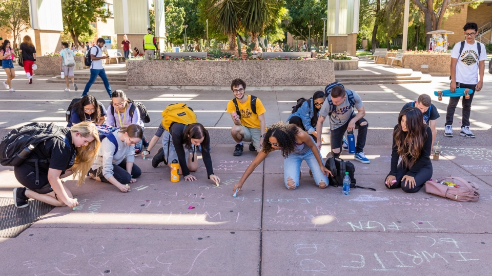 Image of ASU students writing with chalk during National Day on Writing activities 2019, photo by Bruce Matsunaga