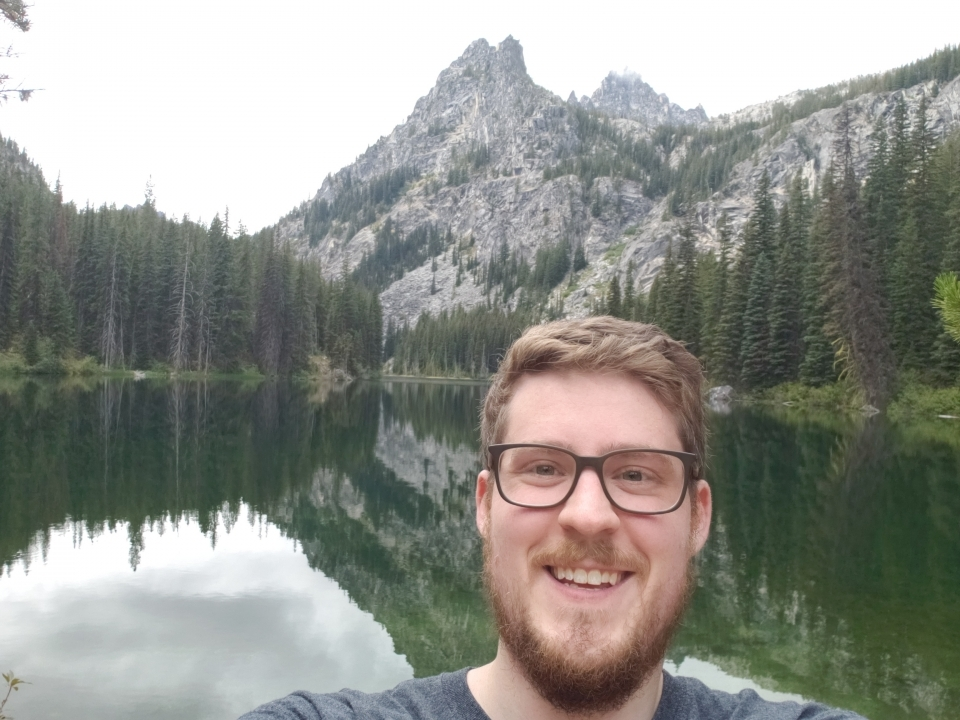man smiling with mountain and trees in the background