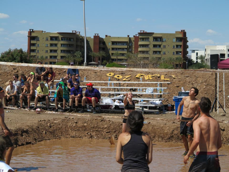 people watching students playing mud volleyball from bleachers