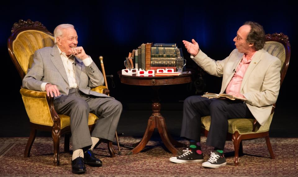 Two men sit in armchairs on a stage.