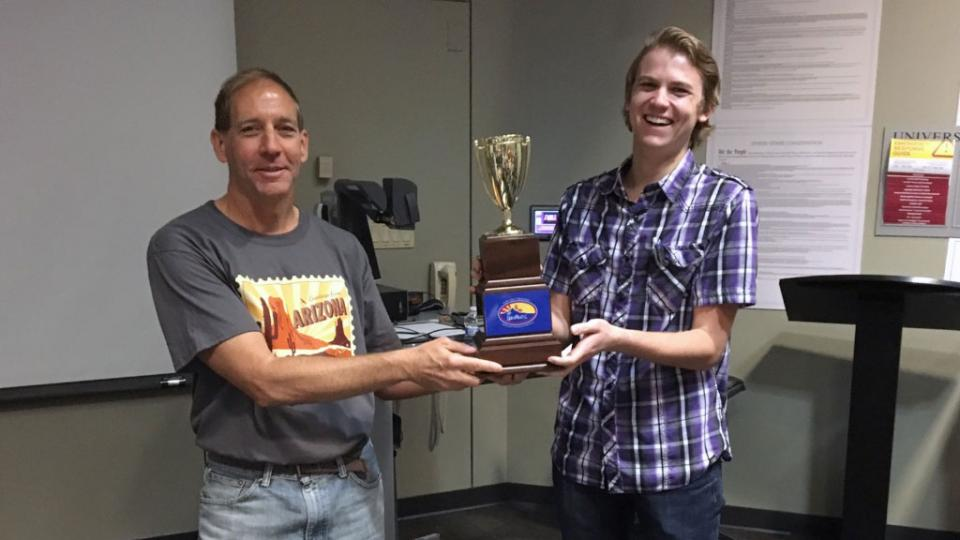 A professor and a student hold a trophy.