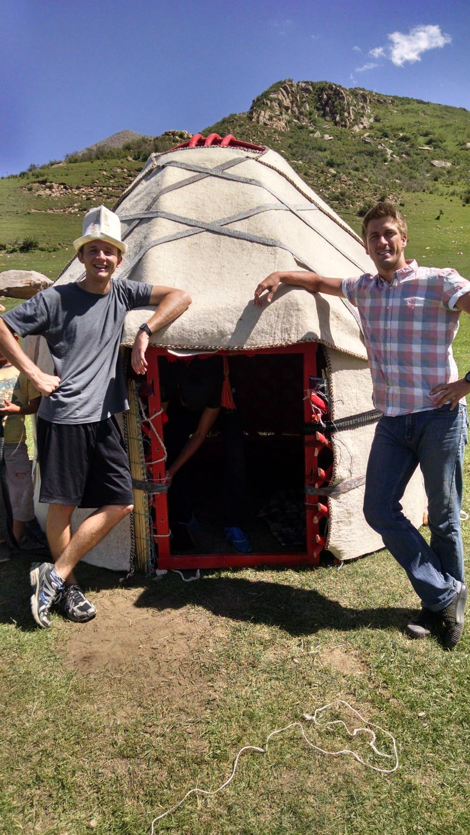 two men standing outside of a yurt