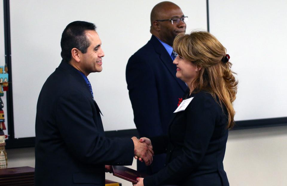 Hector Zelaya congratulates a graduate of the Bob Ramsey Executive Education program at Arizona State University.