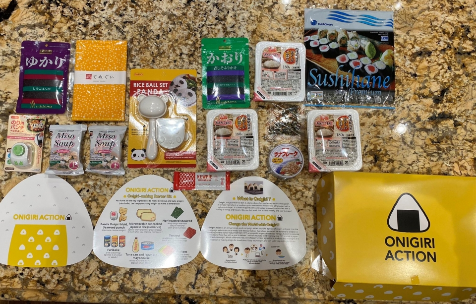 Ingredients and tools for making onigiri, Japanese rice balls, are laid out on a counter. The ingredients include instant rice, canned tuna and sheets of dried seaweed. There is also a rice press that shapes the rice into the shape of a panda.