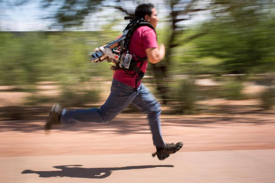 A student wears a jetpack while running.