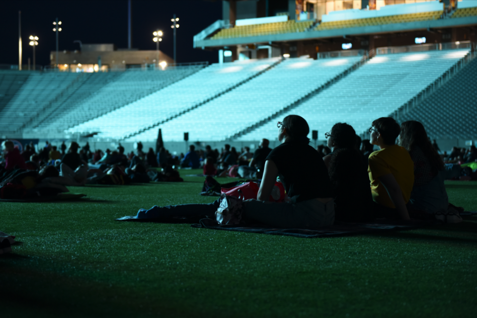 Friends sit on a blanket at Movies on the Field