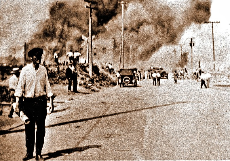 historical photo of a street town with lots of smoke in background
