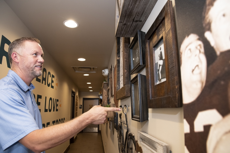 Tim Vasquez shows family photos and black-and-white images of the early days of the restaurant. Today they hang on the walls of Someburros locations around the Valley.